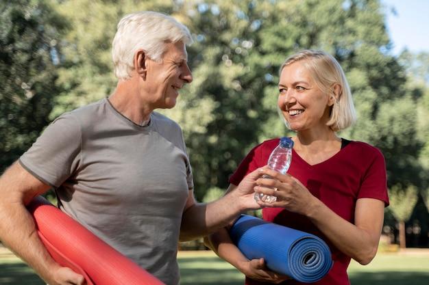 Смайлик пожилая пара на открытом воздухе с ковриками для йоги и бутылкой с водой Бесплатные Фотографии