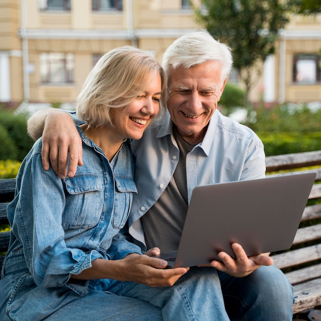 Smiley older couple sitting on bench outdoors with laptop Free Photo