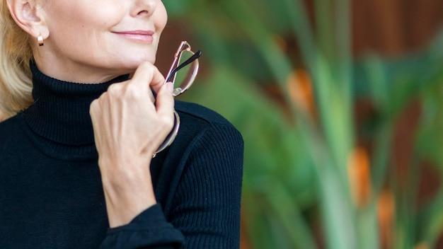 Смайлик пожилая женщина, держащая очки во время отпуска Бесплатные Фотографии