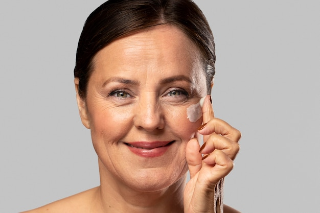 Смайлик пожилая женщина, используя увлажняющий крем на лице Бесплатные Фотографии