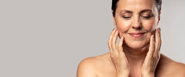 Смайлик пожилая женщина с макияжем позирует с руками на лице и копией пространства Premium Фотографии