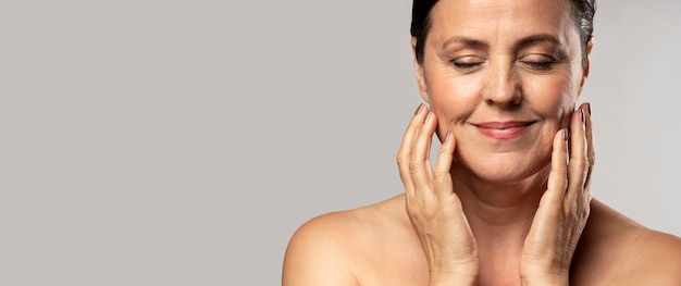Smiley older woman with make-up on posing with hands on face and copy space Free Photo