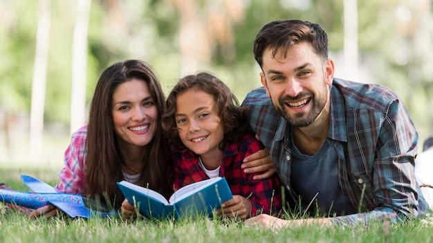 Улыбающиеся родители и ребенок читают вместе Бесплатные Фотографии