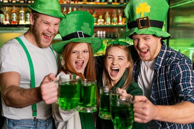 セントを祝うスマイリーの人々。バーでのパトリックの日 無料写真