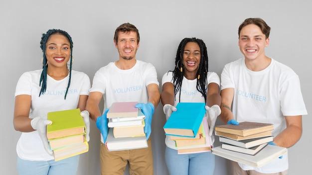 Смайлики держат кучу книг, чтобы подарить им Бесплатные Фотографии