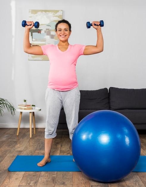 Смайлик беременная женщина упражнениями дома с весами и мячом Бесплатные Фотографии