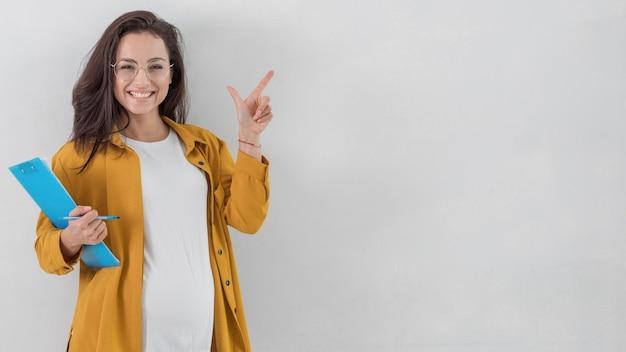 Donna incinta di smiley che tiene appunti e rivolta verso l'alto con lo spazio della copia Foto Gratuite