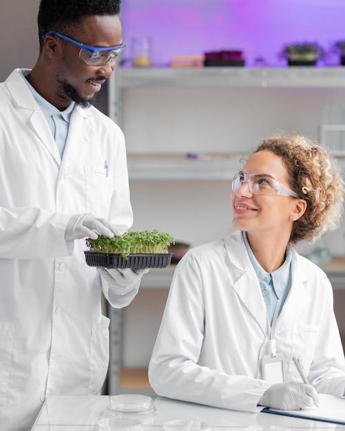 실험실에서 안전 안경을 쓴 웃는 연구원 무료 사진
