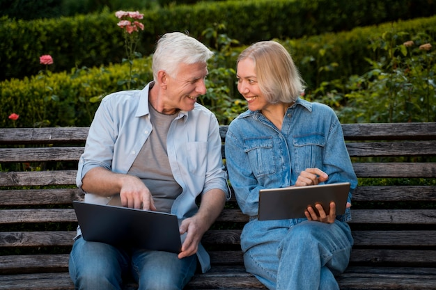 Smiley senior couple outdoors on bench with laptop and tablet Free Photo