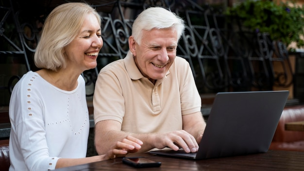 Smiley senior couple sitting down outdoors and looking and laptop Free Photo