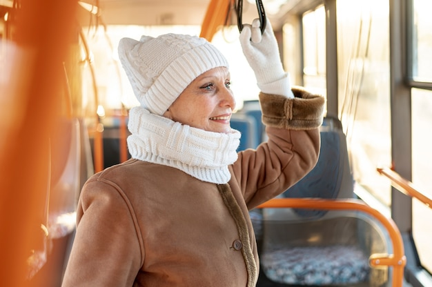 Smiley senior female riding bus Free Photo