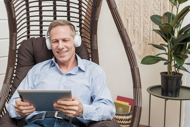 ヘッドフォンも音楽を聴くスマイリーシニア男性 無料写真