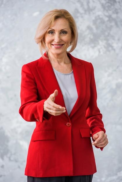 Smiley senior woman giving a hand shake Free Photo