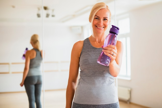 Smiley senior woman holding a water bottle Free Photo