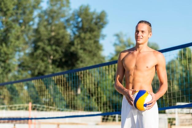 ボールを保持しているビーチでスマイリー上半身裸の男性のバレーボール選手 無料写真