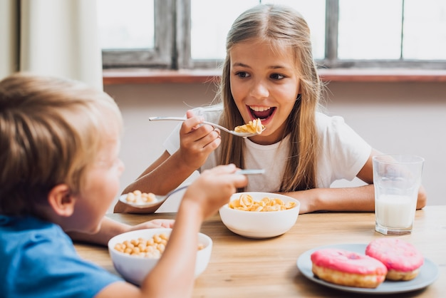 Smiley siblings looking at each other while eating Free Photo