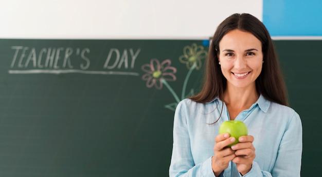 Учитель смайлик держит яблоко с копией пространства Premium Фотографии