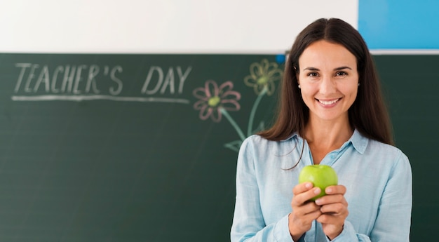 Smiley teacher holding an apple with copy space Premium Photo