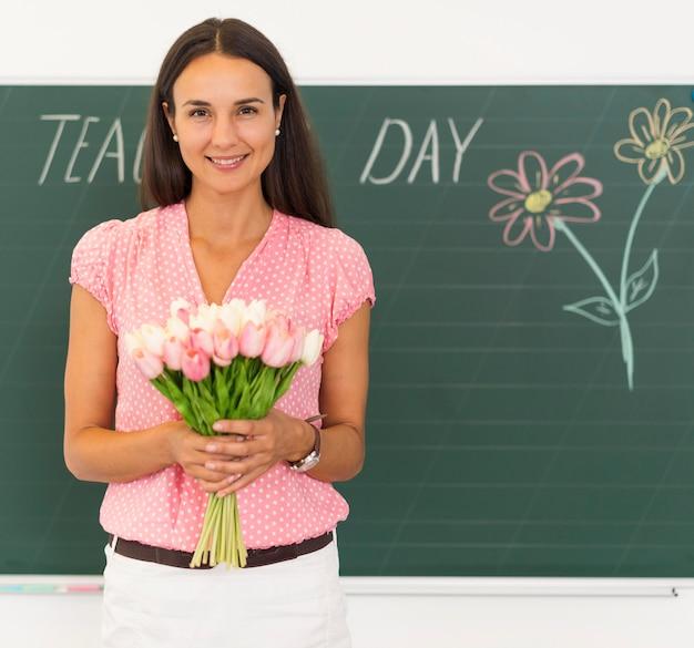 Insegnante di smiley che tiene un mazzo di fiori Foto Gratuite