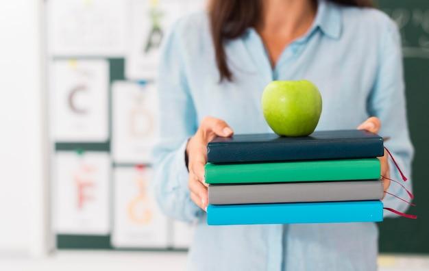 Insegnante di smiley che tiene un mazzo di libri e una mela Foto Gratuite