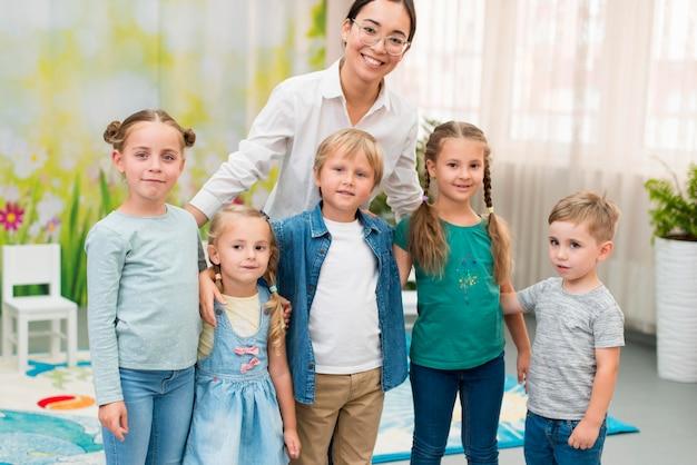 Учитель смайлик держит своих учеников в детском саду Бесплатные Фотографии