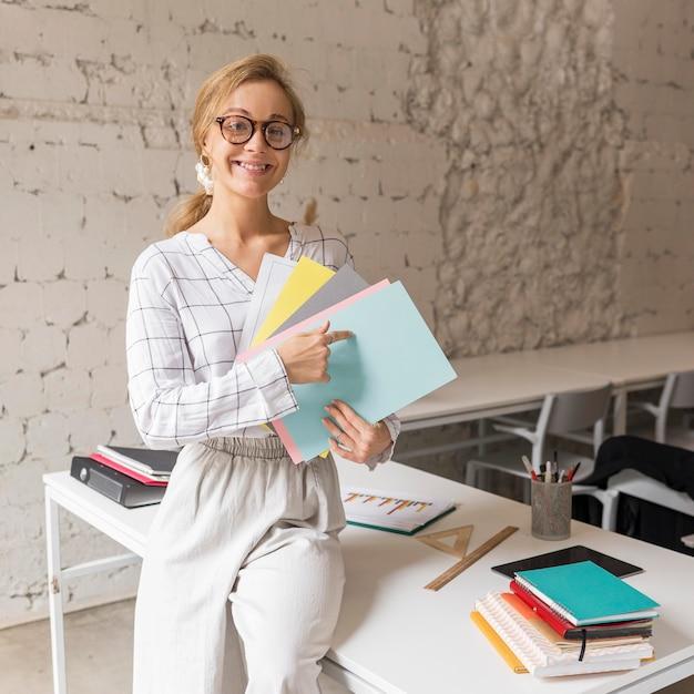 Insegnante di smiley che indica ai libri Foto Gratuite