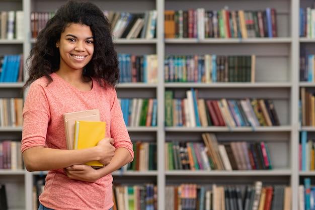 図書館でスマイリー10代の少女 Premium写真