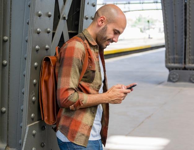 Smiley traveler using mobile Free Photo