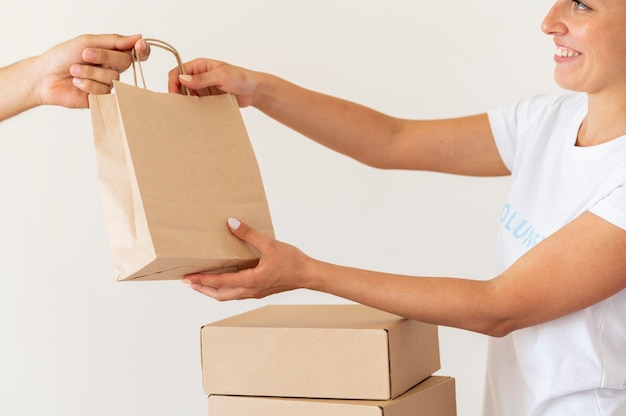 Смайлик-волонтер вручает сумку с пожертвованиями на еду Бесплатные Фотографии