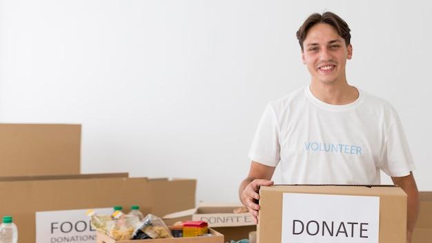 Смайлик-волонтер держит коробку для пожертвований с копией пространства Бесплатные Фотографии