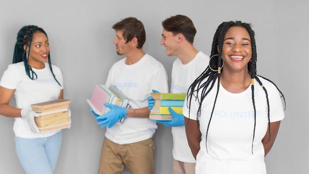 Smiley organizzazione di volontariato che tiene libri per donazioni Foto Gratuite
