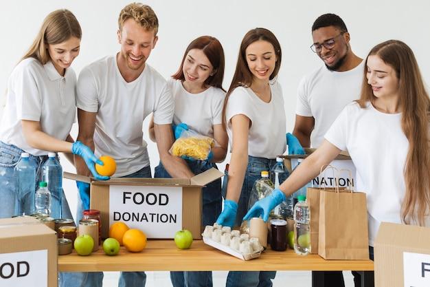Волонтеры smiley готовят коробки с едой для пожертвования Бесплатные Фотографии