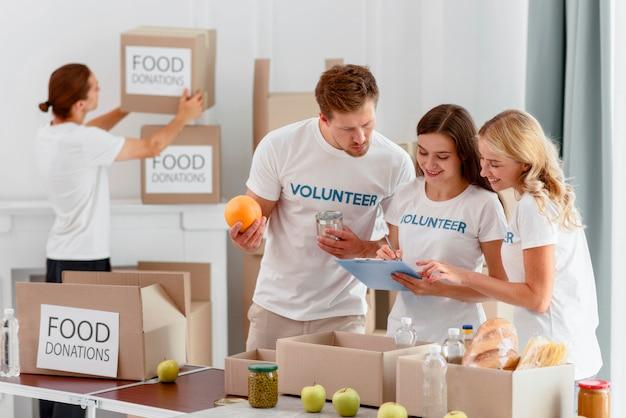 Smiley volunteers preparing food for charity Free Photo