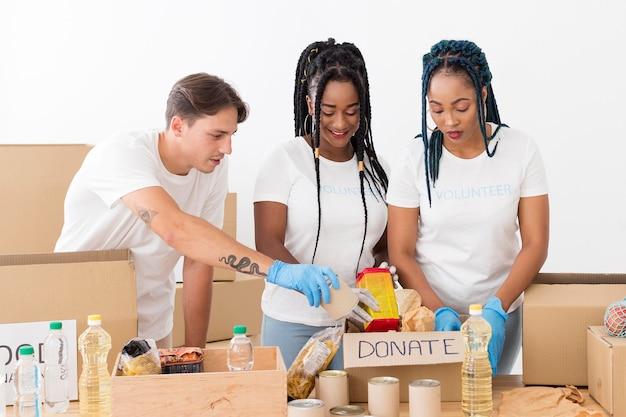 Volontari di smiley che si prendono cura delle donazioni Foto Gratuite