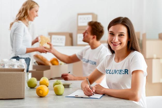 Volontari di smiley che lavorano per donare cibo Foto Gratuite