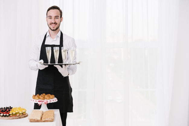 Smiley waiter holding glasses with copy space Free Photo