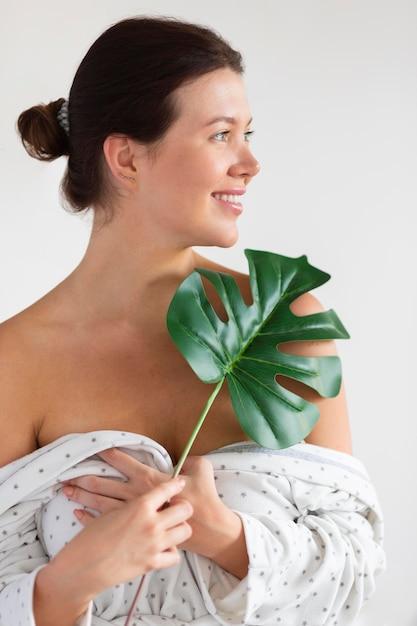 Donna sorridente in accappatoio con foglia Foto Gratuite