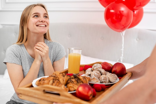 Smiley woman being surprised with breakfast in bed Free Photo