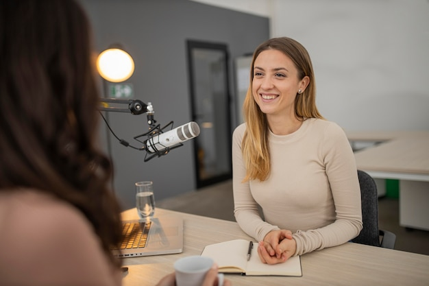 Smiley woman broadcasting an interview on radio Free Photo