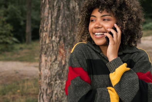 Смайлик женщина, кемпинг на открытом воздухе и разговаривает по смартфону Premium Фотографии