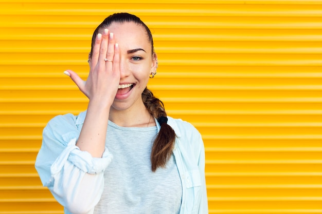 Smiley woman covering an eye Free Photo