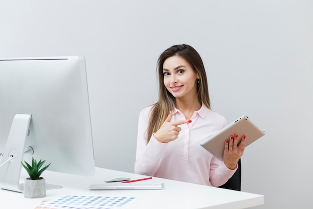 Smiley woman at desk pointing at tablet Free Photo