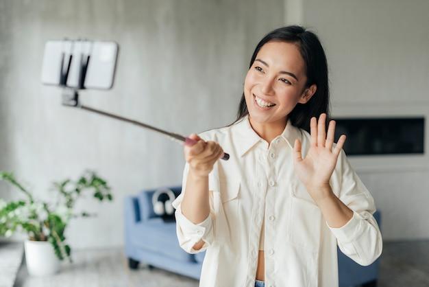 Donna sorridente che fa un vlog a casa Foto Gratuite