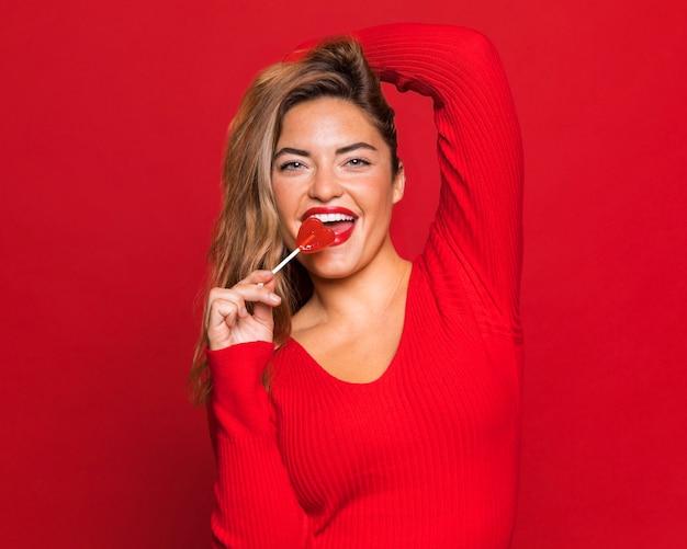 Donna sorridente che mangia lecca-lecca Foto Gratuite