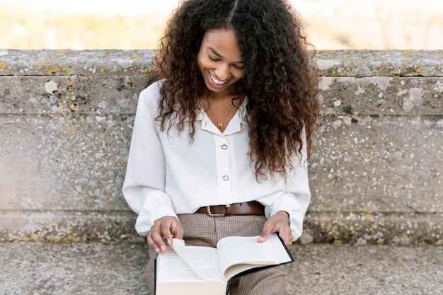 Smiley woman enjoying a book outdoors Free Photo
