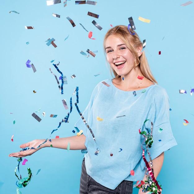 Smiley woman enjoying confetti time Free Photo