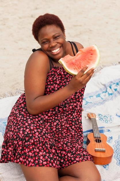 Smiley woman enjoying watermelon at the beach Free Photo