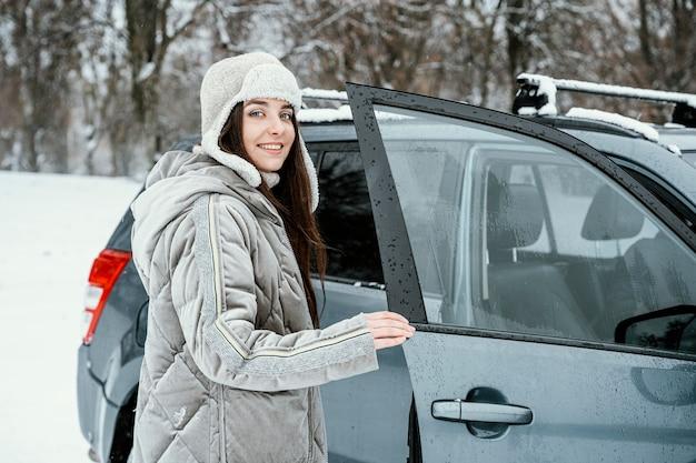 Donna sorridente che torna in macchina durante un viaggio Foto Gratuite