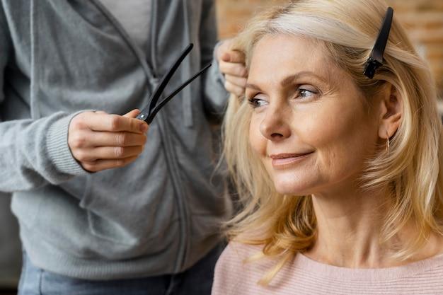 自宅で髪型を取得するスマイリー女性 無料写真