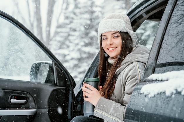 Смайлик женщина выпить теплый напиток и насладиться снегом во время поездки Бесплатные Фотографии
